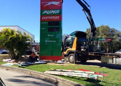 crane truck lifting pylon sign puma on the roadside