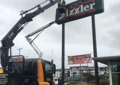 walkabout crane putting up Sizzler on a high roadside signage