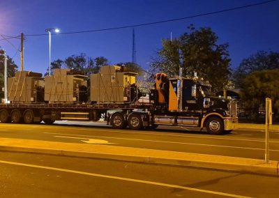 flat top trucks with three large boxes on transit at night