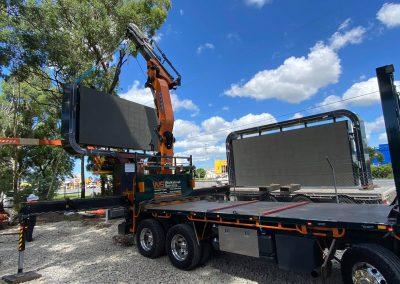 crane truck lifting large rectangle digital signage