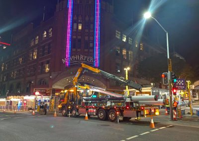 crane truck carrying large pipes for hotel